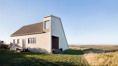 The windswept sand dunes of Quebec's Magdalen Islands informed the outline of this second home for a retired couple, by Bourgeois/Lechasseur Architects.