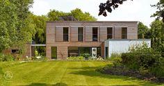 Drei rechteckige Baukörper mit verschiedenen Erscheinungsbildern, Schiebeläden in Fassadenoptik und französische Balkone – Baufritz Bauhaus Russell