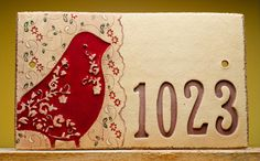 Customize this unique address sign with your house numbers. The texture, large red bird, and flower-themed lacy background offer guests a warm welcome to your home. * * *Please be sure to leave your house number in the notes to seller box during checkout.* * * OVERALL MEASUREMENT Sign (approximate): 16.5 wide x 9.5 tall x 3/4 thick (34.3cm x 24.13cm x 1.91cm) Individual numbers (approximate): 3.75 tall x 1.5 wide ------------------- CUSTOMIZING THIS ITEM *Piece comes with 2 holes for...