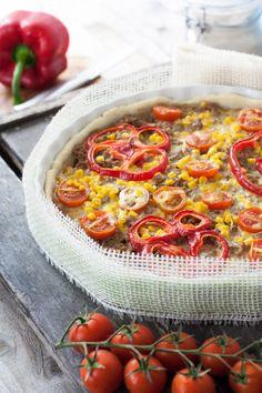 Quiche mexicaine       1 rouleau de pâte brisée (ou pâte maison comme moi!!)     300 grs de bœuf haché     1 oignon      1 petit piment      2 gousses d'ail      2 cuillères à soupe d'huile d'olive      2 cuillères à soupe de concentré de tomates      1/2 à 1 poivron rouge      2 tomates (ou une dizaine de tomates cerises)     1 petite boîte de grains de maïs      2 jaunes d'œufs      20 cl de crème fraîche     poivre & sel      persil