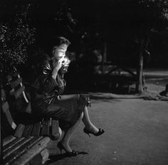 A young woman lighting a cigarette as she sits on a New York park bench at night, circa 1957.