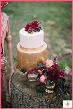 a beautiful gold and white cake topped with an assortment of berries #FallWedding