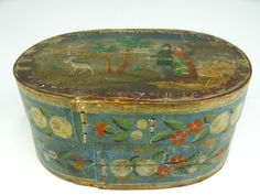 AN UNUSUAL EARLY PAINTED BRIDE'S BOX WITH FIGURES    Measures 8 x 11.5 x 18 inches, oval shaped with original Prussian blue base and full color floral designs on sides. The top section has an unusual scene with figures and a got in landscape with verse around. The lower section bears the more typical floral designs. Museum accessions report states it was brought to America in 1833 and donated in 1933. Includes some of the original notes taped inside by the donor