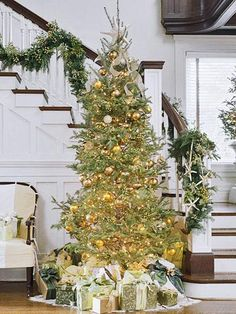 A towering tree commands attention in this entryway. Get the look by hanging several hues of gold-tone balls on your tree, nestling small green berries in between the boughs, and topping the whole thing off with a cascading bow