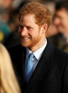 Prince Harry - looking smart in a paisley-print blue tie with matching shirt - smiled as his legions of fans greeted him