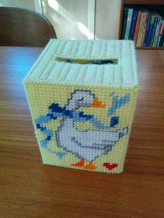What an adorable way to display your Kleenex! This vintage homemade tissue box cover is a sunny yellow color with a picture of a goose (wearing a scarf! with a tiny heart in the corner!) on all four sides. It appears to be made from a plastic canvas needlepoint/embroidery kit. Measures approx. 4 1/2 by 4 1/2 by 5 5/8--fits square tissue box. Good vintage condition with light wear & tear; some yarn fraying. Its cheesy, but in an awesome way