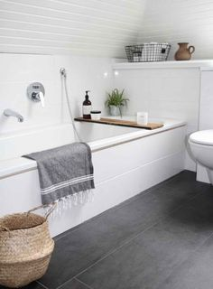 TUB. DARK GREY BIG FLOOR TILES. LONG RECTANGULAR WHITE SUBWAY WALL TILES.
