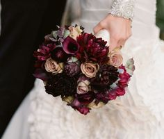 A loose clutch bouquet of plum hydrangeas, burgundy dahlias, red Piano garden roses, Quicksand roses, burgundy scabiosa, burgundy calla lilies, purple succulents, and burgundy ranunculus wrapped in champagne ribbon with the stems showing