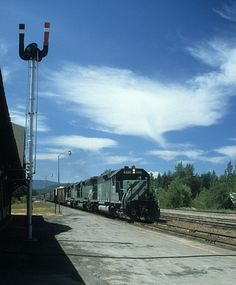 Train 84, with engines 6329, 6496, and 6303, is passing the Burlington Northern station at Belton, Montana on June 26, 1979. Disk 12