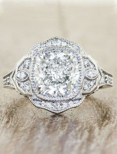 An outstanding 3.50ct cushion cut diamond and is surrounded by delicate hand-engraved and diamond encrusted petals for a stunning, vintage look.