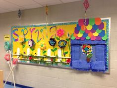 Spring bulletin board using household objects (baby bumper painted blue for the house, bottle cap flowers, etc...)