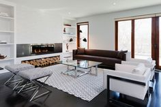 living rooms - white built-ins flanking modern fireplace stacked tiles brown sofa white modern chairs x ottomans white gray rug glass-top coffee table
