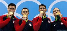 Gold medalists (L-R) Nathan Adrian, Ryan Held, Michael Phelps and Caeleb Dressel kiss their medals on the podium during the medal ceremony for the men's 4x100-meter freestyle at the Rio 2016 Olympic Games at the Olympic Aquatics Stadium on Aug. 7, 2016 in Rio de Janeiro.