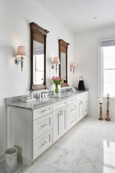 This traditional white master bathroom features white Shaker-style cabinetry with Carrara marble countertops. Durable porcelain tile floors mimic the Carrara marble pattern. The white space is contrasted with rustic Restoration Hardware mirrors and chrome Marble Bathroom, White Master Bathroom, Bathroom Countertops, Marble Countertops, Traditional Bathroom, Carrara Marble Bathroom, Bathroom Floor Tiles, White Marble Bathrooms, Shaker Style Cabinetry