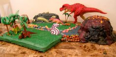 Two sheet cakes, 1 round cut in half for the fossil rock, 4 different sized bundt cakes for the volcano. Add some Coco Puffs and jelly beans for rocks and adorn with toys any little boy who loves dinosaurs has in the house for a cool dino party cake!