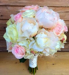 Lovely bouquet of open peonies, roses with white hydrangea peeking through from beneath