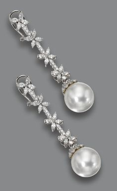 PAIR OF CULTURED PEARL AND DIAMOND PENDANT-EARCLIPS. The long fringes of floral design set with numerous marquise-shaped and round diamonds weighing a total of approximately 3.50 carats, suspending 2 cultured pearls measuring approximately 14.6 by 14.5 mm. and capped with round diamonds, mounted in 18 karat white gold.