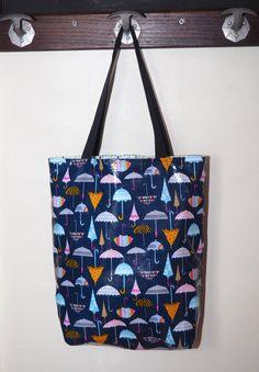 Ce sac cabas imperméable à limprimé originale pourra vous servir comme sac de shopping, sac de cours, où pour le boulot !  A lextérieur, il est en coton enduit imprimé de parapluie multicolores. Lavantage de ce tissu est que vous pouvez le nettoyer dun coup déponge, il est imperméable et résistant. Pour resté dans le thème, il est doublé avec un coton imprimé de gouttes de pluie bleu, grise et verte. A lintérieur, Jy ai cousu une double poche plaqué afin que vous puissiez y ranger votre…