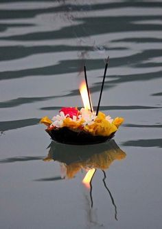 For the departed soul - a lit candle, fresh flowers, incense afloat on a leaf.