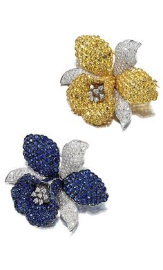 PAIR OF SAPPHIRE AND DIAMOND BROOCHES. Each designed as a stylised orchid, the petals and leaves pavé-set with circular-cut yellow and blue sapphires and brilliant-cut diamonds.