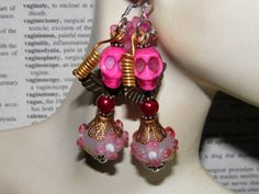 Day of the Dead Angel Earrings with Pink Turquoise Sugar Skulls, Copper Angel Wings, Handmade Lampwork Glass Beads, Burgundy Glass Pearls, and Purple Flowers with Sterling Silver Ear Wires. Handcrafted by MelancholyMind, $14.99