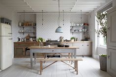 White subway tile, vintage lighting and fridge, and white wooden floors