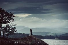 Bride and groom kiss at dusk light, surrounded by the beautiful and dramatic lake and hills of Lake Windermere - The importance of light and planning your photography around it © Babb Photo