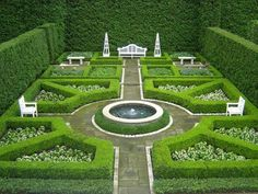 Perfectly manicured hedge garden complete with obelisks, Chippendale fretwork seating, and centered fountain on the grounds of a c1908 brick Georgian revival home in Lake Forest, Illinois.