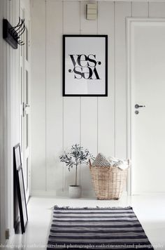 This white entrance hall has several interesting details such as the wall print and striped rug.