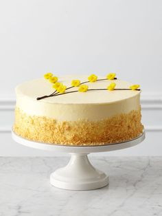 Three layers of vanilla butter cake are laced with homemade lemon curd and raspberry preserves. A smooth coat of white chocolate buttercream, a flurry of vanilla cake crumbs and golden marzipan flowers