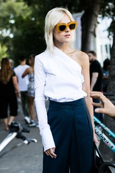 cool oversized sunglasses and one shoulder shirt and wide leg pants create a fashion-...