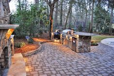 Outdoor kitchen with fireplace and paver patio