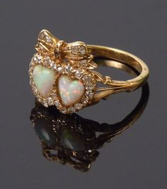 Sworders - Fine Art Auctioneers - An Edwardian opal and diamond twin heart ring, Two heart shaped cabochon opals, surrounded by old eight cut diamonds with a diamond set bow above, trifurcated shoulders to a later shank, marked 18ct. Finger size N¼