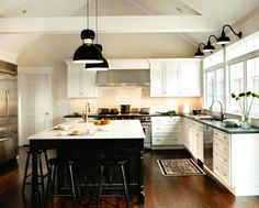 Wall sconces and wood floor, dark countertops and light island countertop