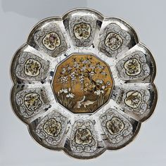 Japanese silver and shibayama dish, the dish is decorated with ten lobed segments around a decagonal central gold lacquer shibayama panel , each section is finely worked in silver wire and inset with a shibayama inlaid ivory tablet, the gold ground central panel is decorated in the finest quality shibayama. The dish itself is made from heavy gauge silver, the underside signed in a mother of pearl tablet, Stagshead Antiques Ltd. Courtesy Olympia International Art & Antiques Fair Japanese Beauty, Japanese Art, Aesthetic Objects, Antique Fairs, Ropes, Plate Sets, Amazing Art, Persian, Antique Silver