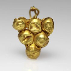 mold-make central front panel with large granules arranged to form a grape, a twisted loop wire at the back. Romans often used a grape motif in their art, especially jewelry. Significant to Roman ever