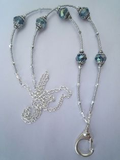 Visit www.lanyardelegance.com Fancy lanyard with Silver highlights and a beautiful Blue Crystal.