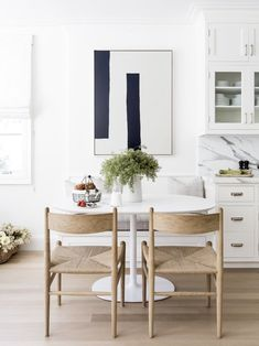 White and wood kitchen with marble countertops and backsplash and modern art and furniture-Alyssa Kapito
