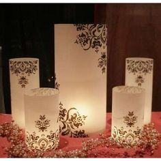 Frosted hurricanes painted with damask stencil. Gorgeous luminaries, the key to luminaries is to make sure your candle is down low so it lights up the whole cylinder.