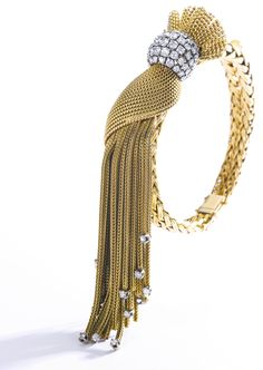 Gold and diamond bracelet, 1950s The center of bombé design, set with brilliant-cut diamonds, suspending a tassel highlighted with similarly-cut diamonds, inner circumference approximately 145mm, partial French maker's marks.