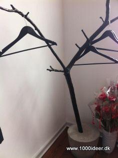 """Det naturlige her ligger i, at stumtjeneren er lavet ud af en kraftig gren, der er malet sort. Den står solidt, fordi den er """"plantet"""" i en gang cement, eller måske er det beton. Så kom ud i naturen og find den gren, der kan holde til et vis antal bøjler med både sommer- og vintertøj. Ideen er set på Sletten Kro."""