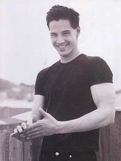 Keanu Reeves rubbing his hands looking cute with a devious smile