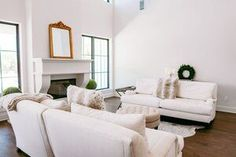 New Build Modern Farmhouse Home Tour with Holly Christian Hayes - Living Room - Minimalist Design - Minimal Home Design - Home Decor - Interior Design - White Sofas - Cow Hide Sofa - European Farmhouse - Black Framed Windows with White Walls - Gold Mirror on Mantle
