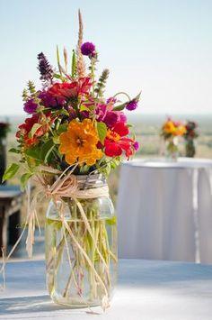 Mason jar flower arrangement with raffia bow and farm-grown flowers