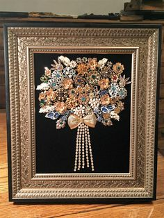 This elegant rhinestone flowered art design made with Vintage Costume Jewelry has been hand glued onto black velvet. Housed in a new ornate frame that is Black with gold accents measures approx. 12x14 with an opening approx. 8x10. This piece would make a perfect compliment to any