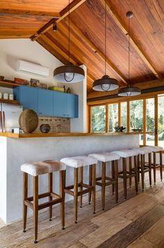 Decoração de casa de campo com madeira. Na cozinha armarios azuis, banquetas de madeira estofadas, luz natural e janelas de madeira. #casasdecampo