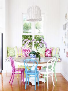 Colorful dining nook - painted chairs (thrift store finds?) and easy banquet seating with pillows.