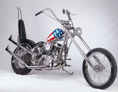 The Captain America is a custom motorcycle best known for its role in Easy Rider. See photos and specifications for this Harley-powered chopper. Motos Harley Davidson, Davidson Bike, Classic Harley Davidson, Chopper Motorcycle, Bobber Chopper, Motorcycle Art, Motorcycle Quotes, Motorcycle Garage, Bike Art