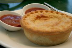 An Australian or New Zealand meat pie is a hand-sized meat pie containing largely diced or minced meat and gravy, sometimes with onion, mush. Australian Meat Pie, New Zealand Food, Meat Pies, Empanadas, Gravy, Onion, Pudding, Desserts, Recipes