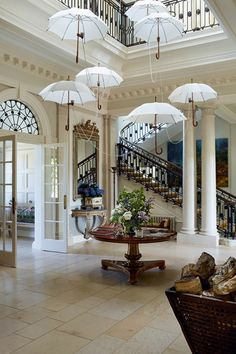 An umbrella lighting installation by Rolf Sachs adds drama to the entrance hall of this Hampshire country house.